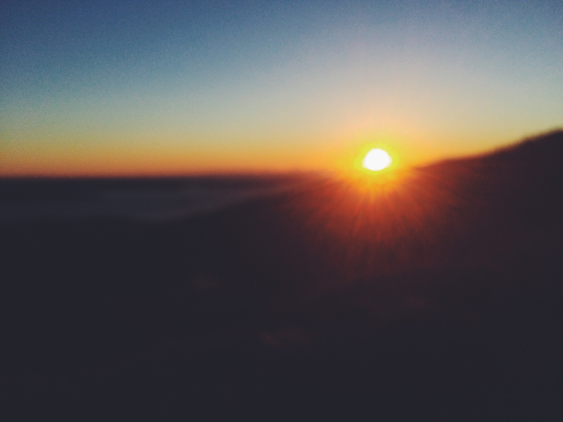 Photograph of the sun rising over mountains.