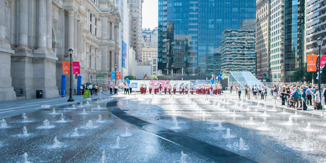 Urban Engineers case study: Photograph of Dilworth Park's play fountain, a 185 by 60 foot water feature with programmable three-foot-high vertical streams. City Hall is to the left and people are gathered towards the south side of the park.