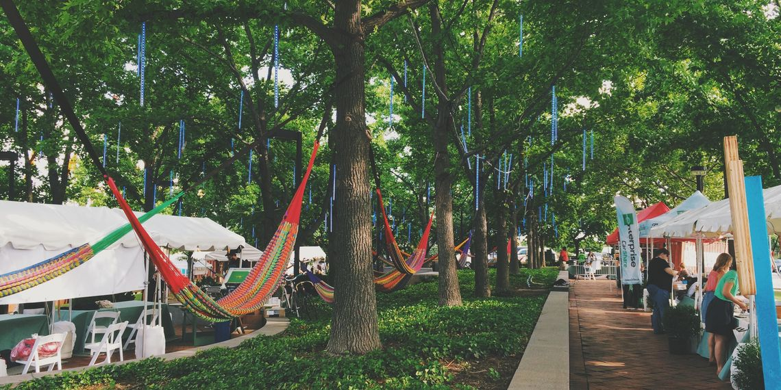 Delaware River Waterfront Corporation case study: image of DRWC's summerfest, with tents of vendors and hammocks hung between trees.