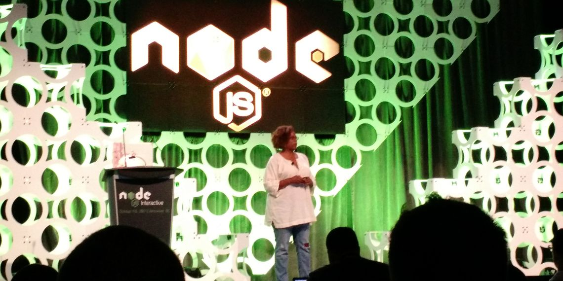 Photograph of Kim Crayton presenting on inclusion in tech at NodeJS 2017, on the stage illuminated with bright green NodeJS logo