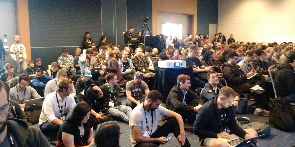 """Photograph of the room packed for the talk """"Understanding and Debugging Memory Leaks in Your Node.js Applications"""" by Ali Sheikh of Google. All the chairs are full and participants are sitting on the floor."""