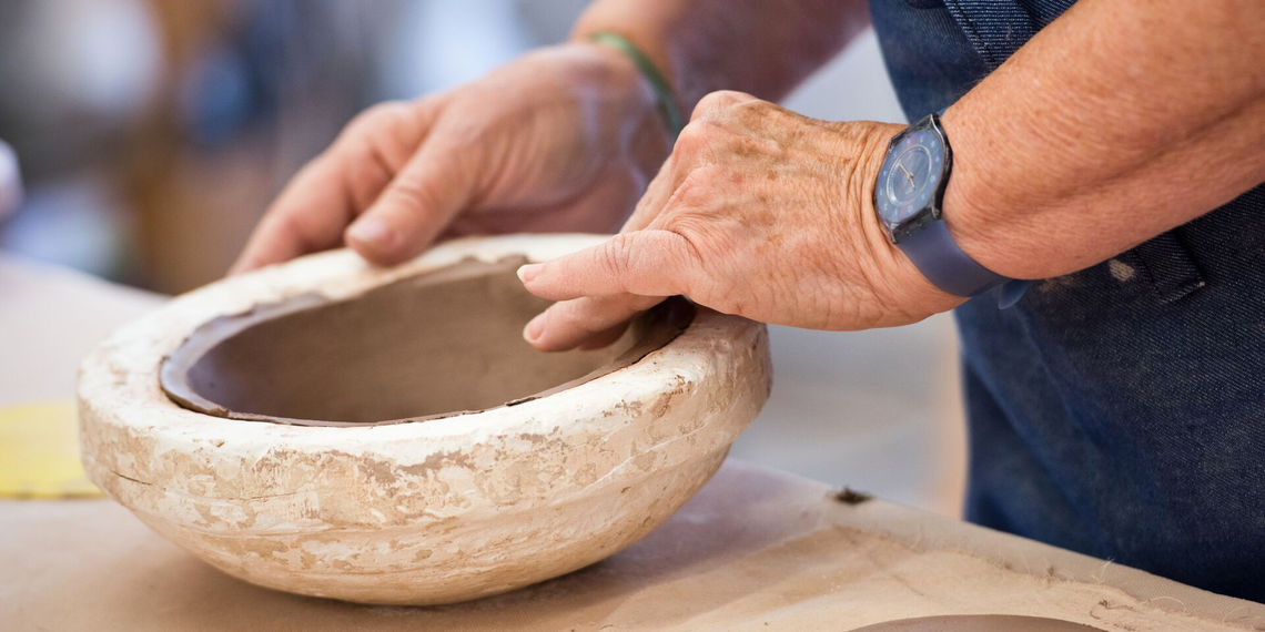 The Clay Studio case study: Photograph of a clay artist shaping a bowl.