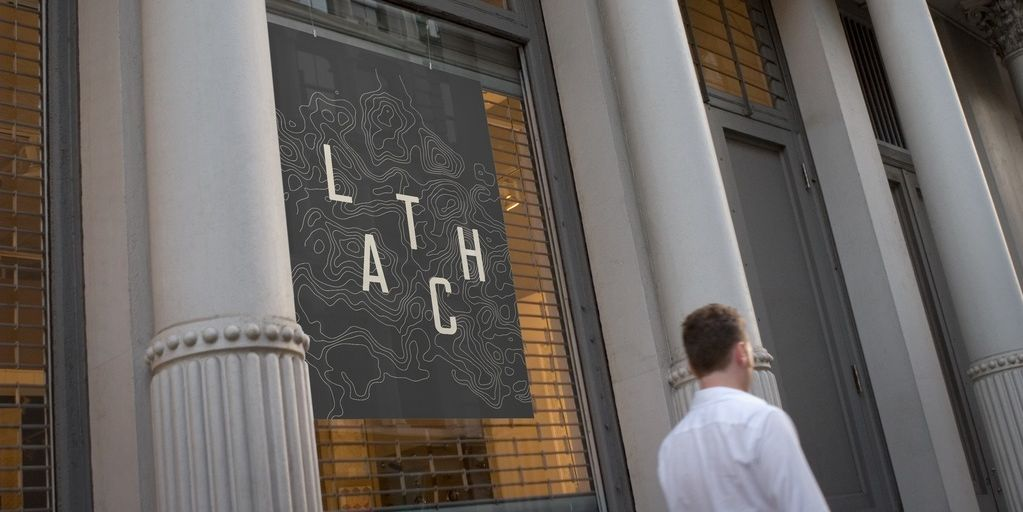 LATCH case study: the letters of LATCH in white against a dark grey banner with darker contour lines, as with a topographic map. The banner is shown hanging between the columns of a city building.